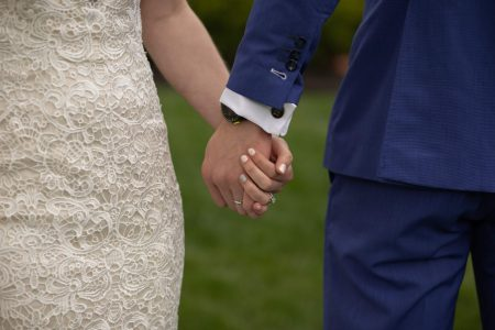 wedding suit holding hands